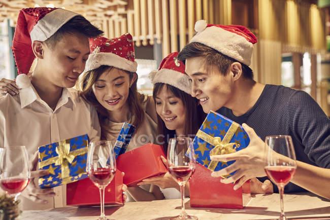 Счастливые молодые люди и их друзья вместе празднуют Новый год в кафе и делятся подарками — стоковое фото