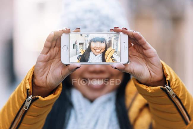 Jovem atraente asiático mulher tomando selfie no rua — Fotografia de Stock