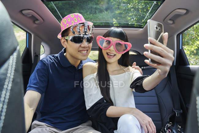 Giovane coppia che si fa un selfie sul sedile posteriore di una macchina — Foto stock