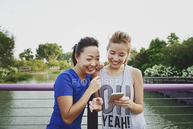 Young asian women using smartphone outdoors — Stock Photo