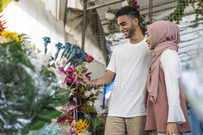 Joven pareja musulmana comprando flores . - foto de stock