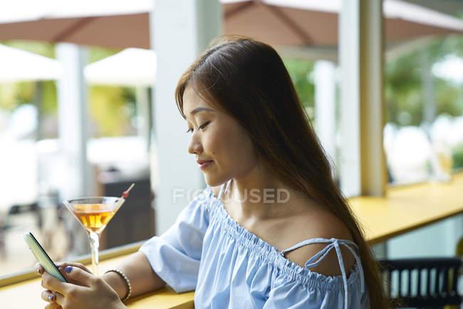 Приваблива молода жінка азіатських за допомогою смартфона — стокове фото