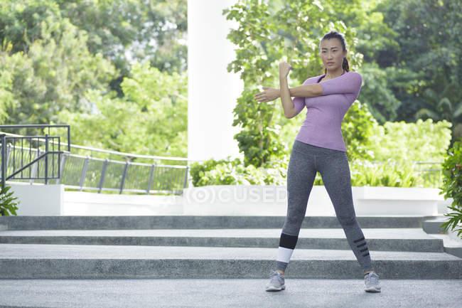 Uma jovem mulher asiática está se alongando antes de seu treino de corrida diária na cidade de Singapores . — Fotografia de Stock
