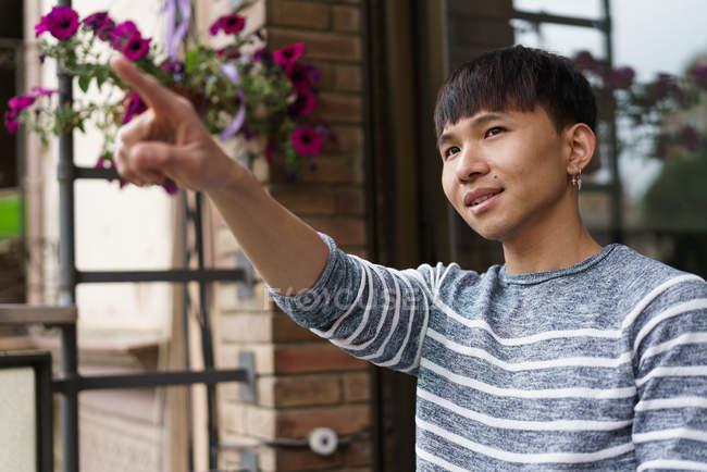 Joven adulto asiático hombre apuntando en algo - foto de stock