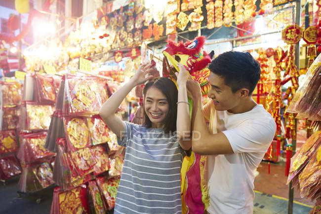 Young asian couple spending time together on traditional bazaar at Chinese New Year — Stock Photo