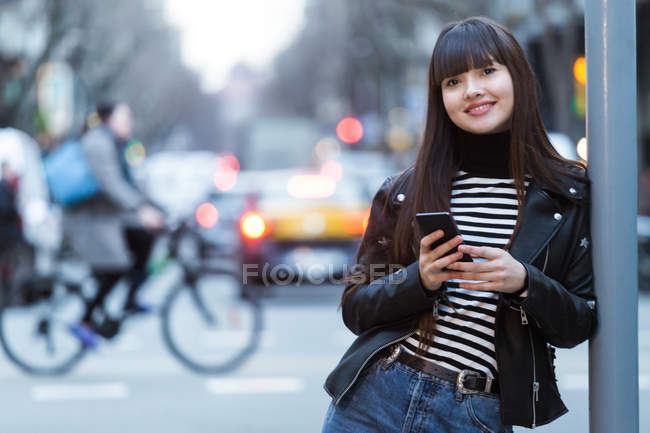Young attractive asian woman in city using smartphone — Stock Photo