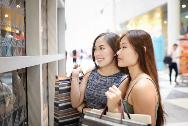 Joven atractivo asiático mujeres con compras bolsas - foto de stock