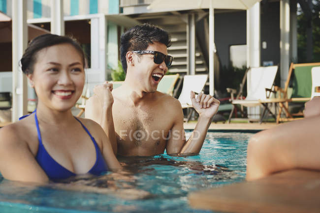 Beautiful young asian friends relaxing in pool — Stock Photo