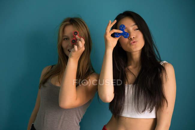 Donna cinese che gioca a spinner con un amico in uno sfondo blu . — Foto stock