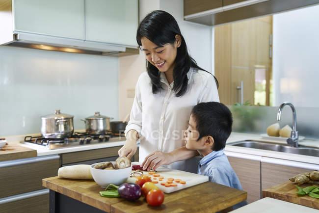 Feliz jovem mãe asiática e logo cozinhando na cozinha — Fotografia de Stock