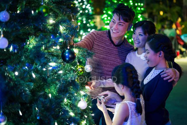 Счастливая азиатская семья проводит время вместе в парке развлечений на Рождество — стоковое фото