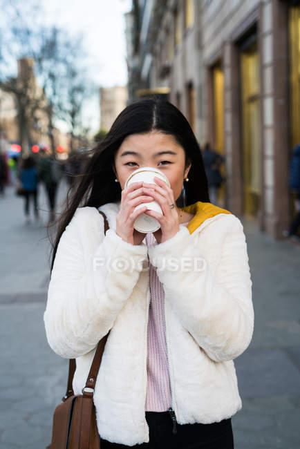 Jovem chinesa bebendo café nas ruas de Barcelona — Fotografia de Stock