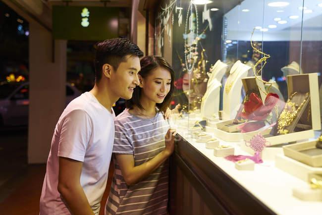 Giovane coppia asiatica in cerca di gioielli in negozio — Foto stock