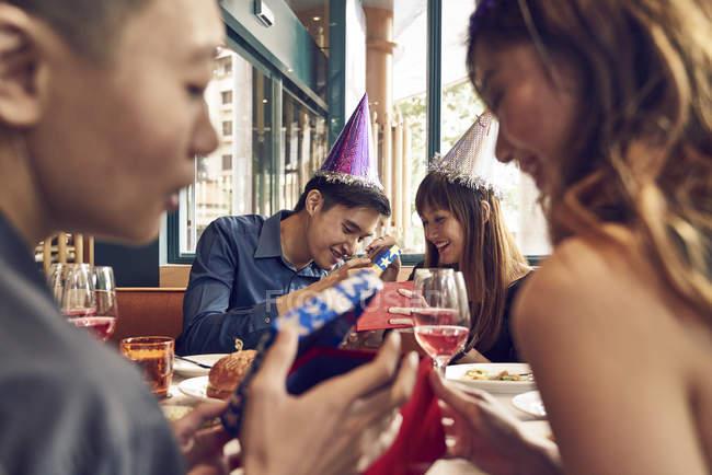 Щасливі молодих азіатських друзі святкування Різдва разом у кафе — стокове фото