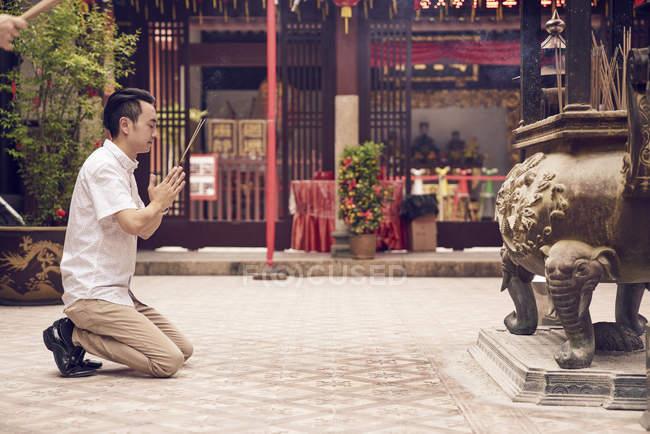Vista lateral del joven asiático rezando en templo con los palillos de los joss - foto de stock