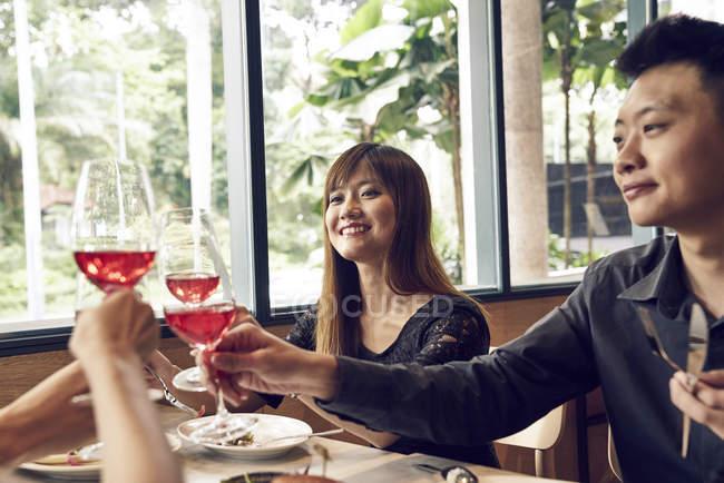 Счастливые молодые люди с друзьями в кафе и веселым вином — стоковое фото