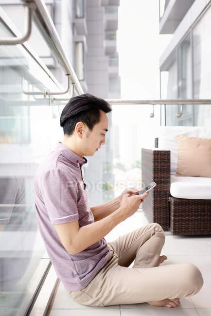 Взрослый азиатский мужчина, использующий смартфон дома — стоковое фото