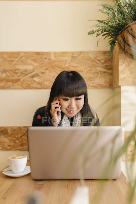 Young attractive asian woman using smartphone in cafe — Stock Photo