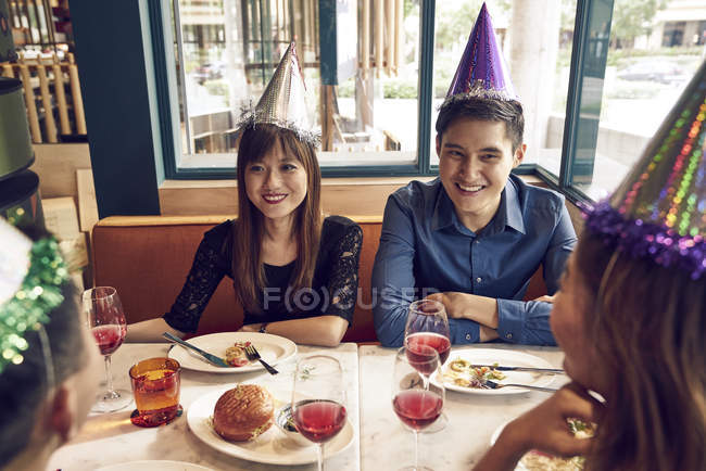 Happy young asian friends celebrating christmas together in cafe — Stock Photo