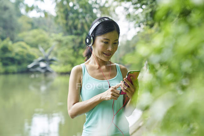Portrait of middle aged woman listening to music while walking in Botanic Gardens — Stock Photo