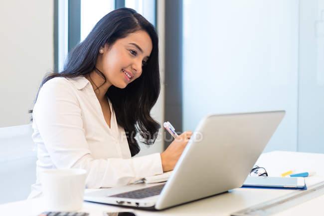 Молодая женщина за работой в конференц-зале делает заметки в современном офисе — стоковое фото