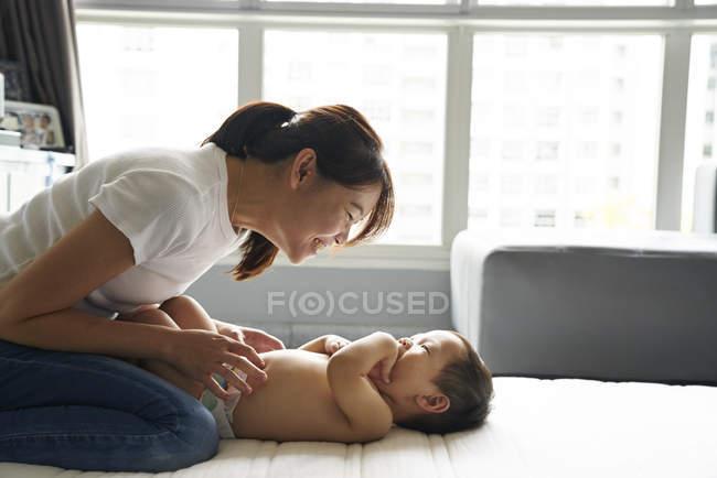Mãe, trocando fraldas para o filho dela adorável — Fotografia de Stock