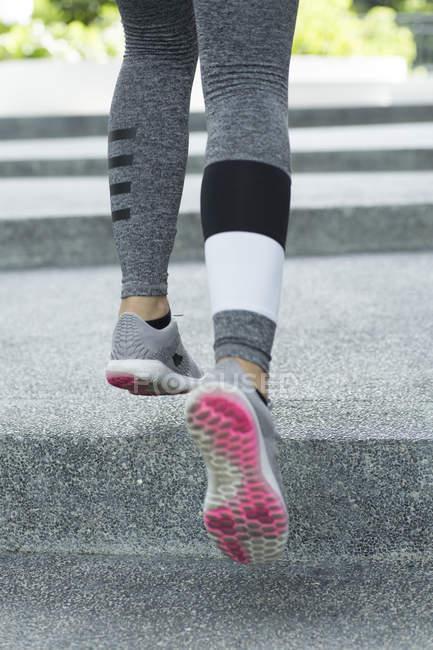 Обрезанный образ ног, бегущих по бетонным ступеням на улице . — стоковое фото