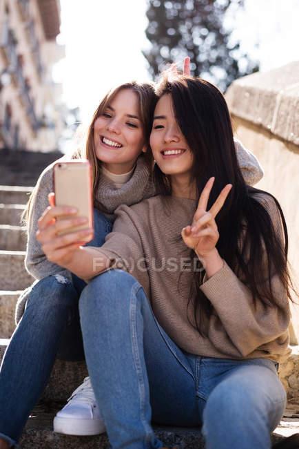Les femmes chinoises et européennes prenant un selfie drôle assis dans une voie stellaire — Photo de stock