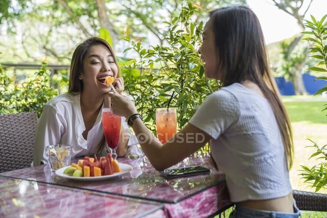 Две юные леди наслаждаются фруктами . — стоковое фото