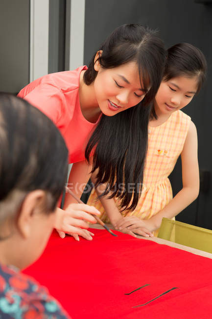 Happy asian family drawing calligraphy hieroglyphs at chinese new year — Stock Photo