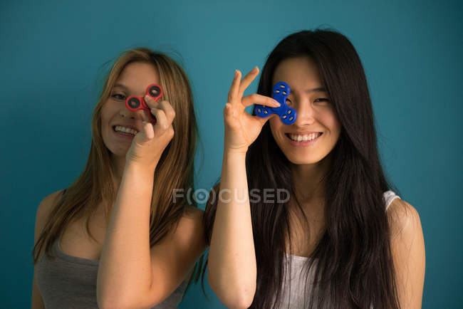Chinese woman playing spinner with a friend in a blue background. — Stock Photo