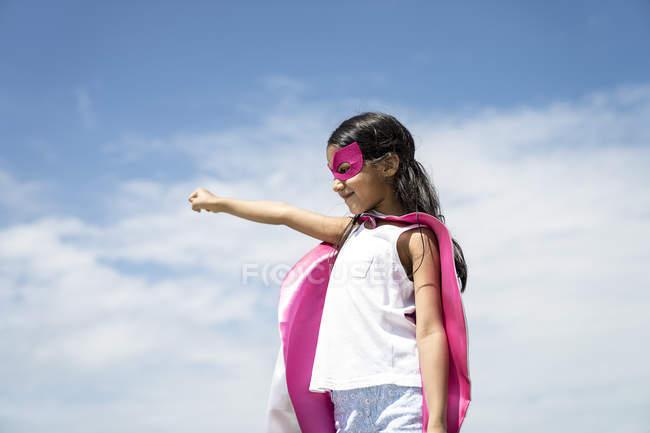 Молодая маленькая милая азиатская девочка позирует в костюме супергероя на фоне голубого неба — стоковое фото