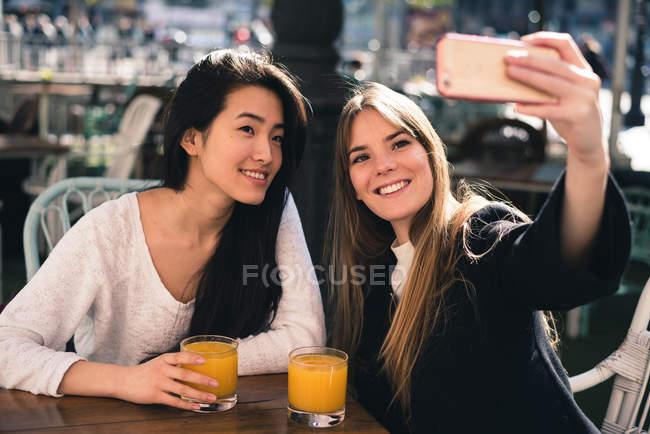 Zwei schöne Freundinnen machen Selfie mit dem Smartphone im Café — Stockfoto