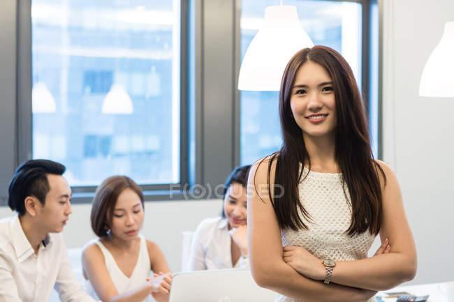 Молодые азиатские коллеги работают вместе, женщина позирует перед камерой в современном офисе — стоковое фото