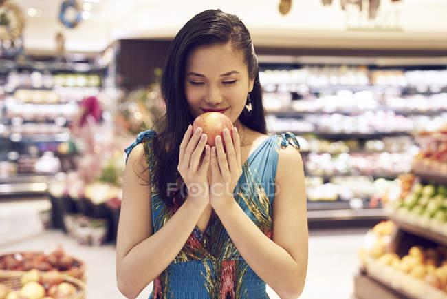 Giovane bella asiatico donna odore mela in negozio — Foto stock