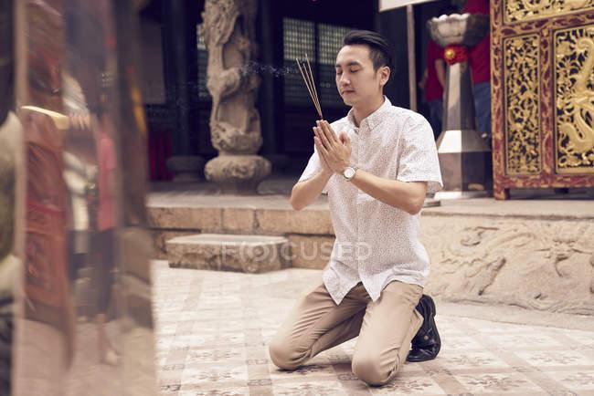 Joven asiática rezando en templo con los palillos de los joss - foto de stock
