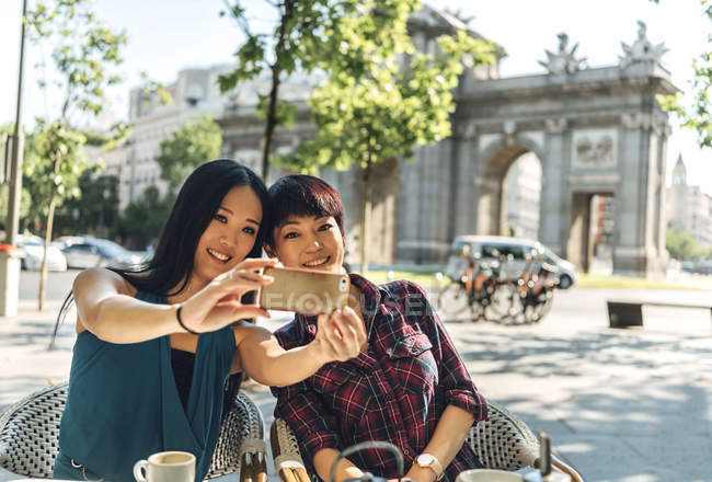 Donne turistiche giapponesi e cinesi che fanno selfie in terrazza vicino alla Puerta de Alcala a Madrid, Spagna . — Foto stock