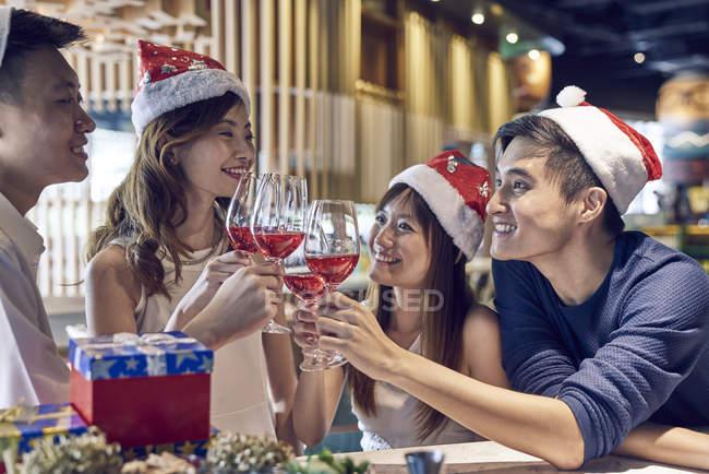 Счастливые молодые азиатские друзья празднуют Рождество вместе в кафе и приветствуя вино — стоковое фото