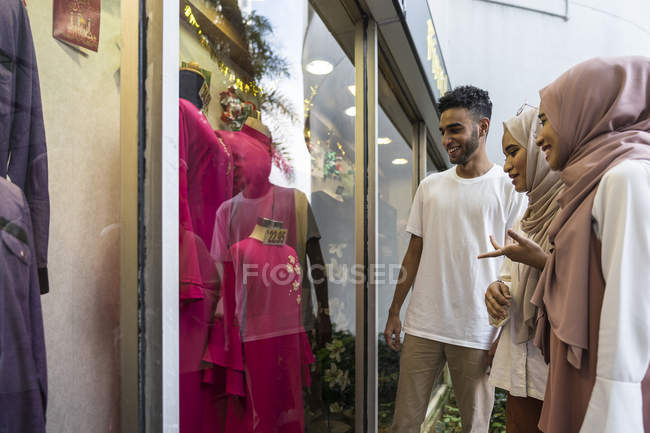 Grupo de amigos muçulmanos felizes compras e olhando a vitrine de loja — Fotografia de Stock