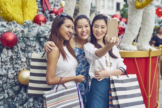 Молодий привабливою азіатських жінок на різдвяні покупки беручи selfie — стокове фото