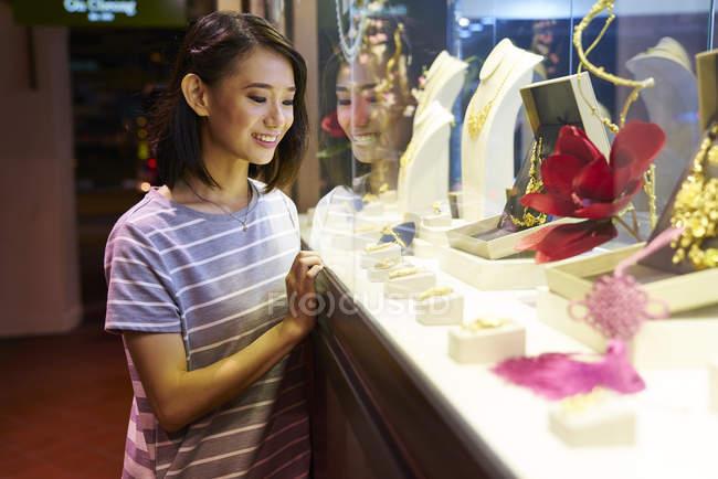 Giovane donna asiatica in cerca di gioielli in negozio — Foto stock