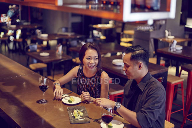 Young attractive asian couple having date in cafe — Stock Photo