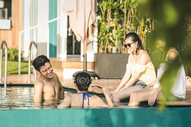 Amici che si divertono in piscina in un beach club — Foto stock