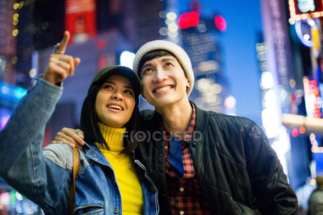 Young asian couple in time square, woman pointing up, New York, USA — Stock Photo