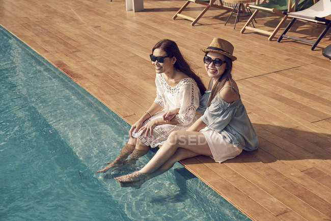Atractivo joven asiático mujeres relajarse cerca de piscina - foto de stock