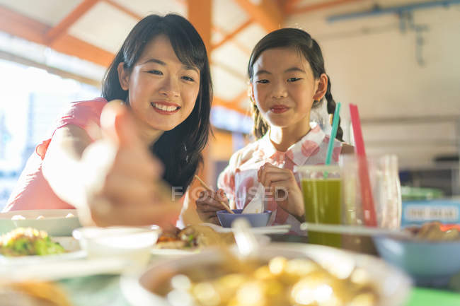 Young asian mother and daughter eating in cafe — Stock Photo