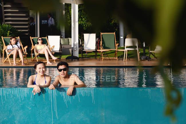 Bella giovane asiatico coppia relax in piscina — Foto stock