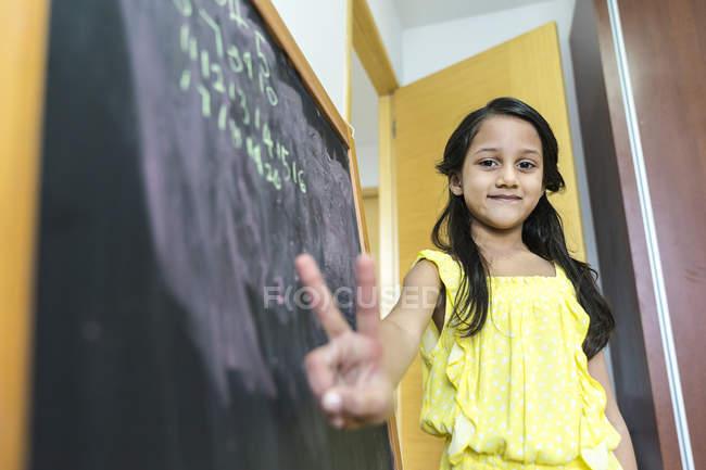 Молодая маленькая милая азиатская девочка в школе рядом с доской — стоковое фото