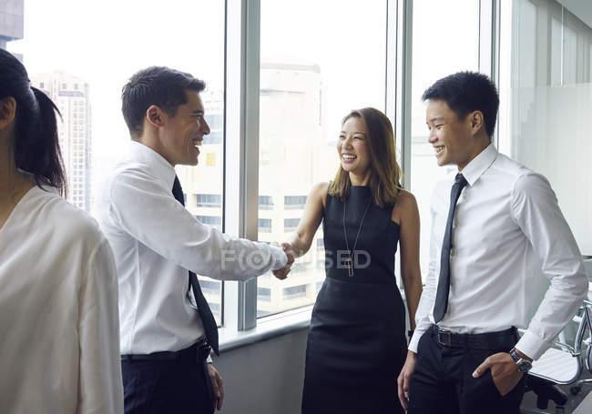 Giovani asiatici uomini d'affari stringendo la mano in ufficio moderno — Foto stock