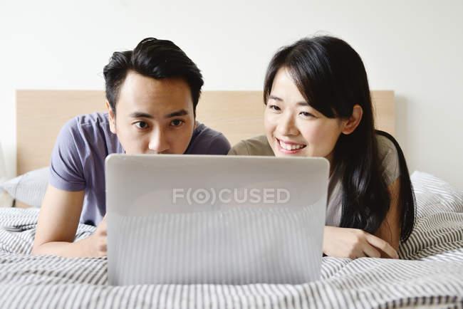 Casal asiático adulto juntos usando o laptop em casa — Fotografia de Stock